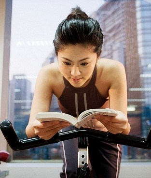 woman reading while biking